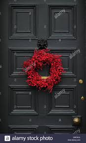 Christmas wreath hanging on front door of traditional English ...