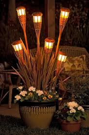 brighten up your outdoor entertaining space with a planter filled with bamboo solar lights