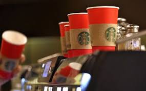buzzfeed posts theory that starbucks holiday cups might have a  a barista reaches for a red paper cup as more cardboard liners already attached