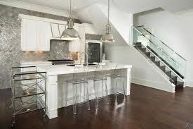 Modern Kitchen With White Cabinets, Metal Backsplash, Engineered Hardwood  Floors, And Chrome Pendant