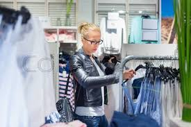 stock image of woman ping clothes per looking at clothing indoors in