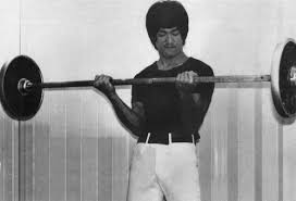 bruce lee doing bicep curls with a barbell