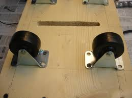 a close up of the caster wheels and belt slot