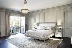 bedroom also area rug balcony doors bedside table chandelier crown molding crystal chandelier french doors mirrored furniture neutral colors nightstand