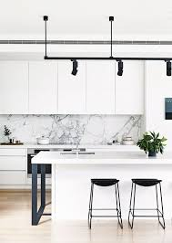 modern white kitchen. A Modern White Kitchen With Marble Backsplash, Black Stools, Lamps And  Legs R