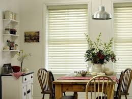white faux wood venetian blinds in white kitchen with wooden dining table and chairs