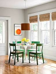 woven wood shades in the breakfast room with green chairs