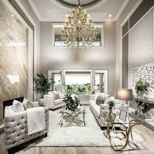 cream wall paint light wood floor white large rug gold chandelier light cream oned sofa metal tables glass top potted plants large windows white pillows