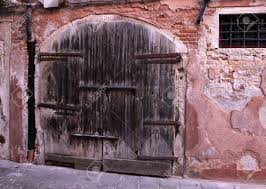 a very old large wooden double door with a large lock stock photo 13803320