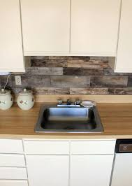 cream sleek cabinets a light colored wood countertop and a backsplash of reclaimed wood