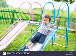 Little Asian kid playing slide at the playground under the sunlight in  summer, Kids play on school yard. Happy kid