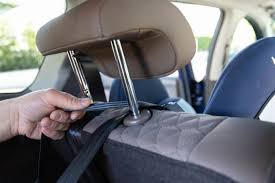 if your car has adjustable headrests lift the headrest up and thread the tether strap over the backrest ensuring it takes the most direct path either
