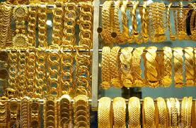 close up of gold bracelets and large chains in the jewelry on the grand