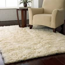 cool flokati rug with armchair and side table also hardwood flooring and window treatment