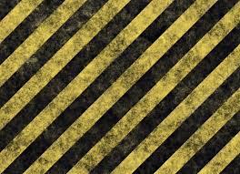 grunge yellow and black hazard stripes wallpaper or background texture