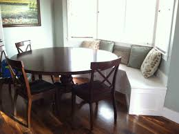 white banquette with cabinet soft colored pillows round dark brown varnished wooden table wooden chairs big painting