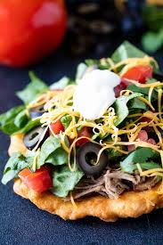 authentic indian fry bread topped with pulled pork greens diced tomatoes cheese