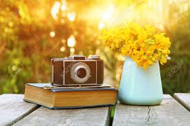 old book vine photo camera next to field flowers on wooden table outdoors at afternoon