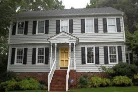 grey house black shutters yellow door with bricks