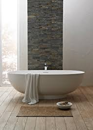 interior white small freestanding bathtub on wooden floor connected by grey stone wall stunning