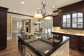 kitchen with brown cabinets and light color counter with white cabinet island with black granite countertops