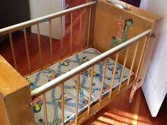 retro baby furniture. antique folding portable baby crib from the 1930s with decals on both ends inside and retro furniture