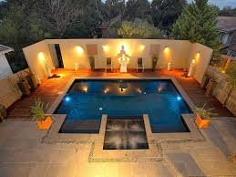 modern lighting look in yellow shade landscape lighting design in front of outsize pool with wooden deck and two small chairs also three white statues