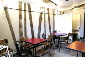 Reclaimed wood wall treatment with industrial exposed lighting at  Hazelsprings Organic Bakery, an industrial coffee