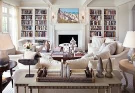 one kings lane alexahampton pale white on white warm paint colors living room with classic fireplace mantel and built in bookcases