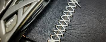 hand sewing two leather pieces with a cross stitch pattern