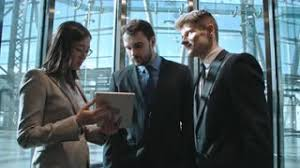 people talking in elevator. two young businessmen and asian businesswoman moving up in the elevator modern business center: people talking