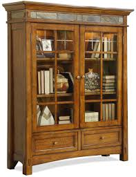 warm brown wooden bookshelves with dual swing glass doors plus round knobs and short legs plus accented top