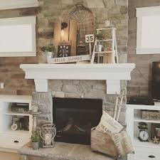 living room decor rustic farmhouse style featuring stone clad fireplace large chunky white wood mantel built in shelving on either side of the fireplace