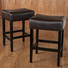 comfortable dark brown wooden backless counter stools with dark leather seats on light brown wooden floor