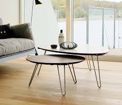 modern round walnut coffee table shown with a corian topped plectrum shaped coffee table