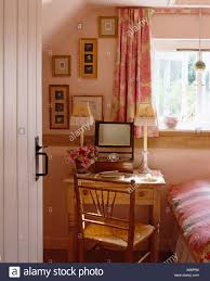 Door open to pink cottage bedroom with pink curtains on window above ...