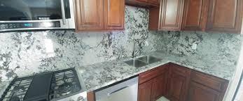 light color granite countertops kitchen countertop with backsplash and dark cabinets close up