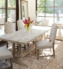 glossy white leather dinng chair near sleeky big wooden table inside large gl window
