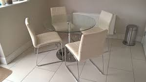 round glass dining table with four white leather chairs