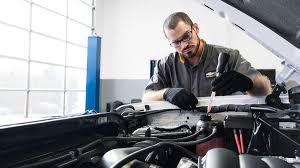 service technician working under the hood of a car