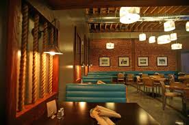 stunning seafood restaurant decorating ideas with exposed brick walls and exposed ceiling beams featuring chic faux blue leather seating booth plus glossy