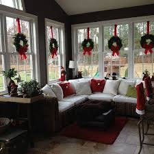 sunroom lighting. love the wreaths suspended with red ribbon in windows of this sunroom decorated for lighting