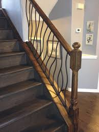 BENT iron design interior railing with a distressed wood handrail and base  rustic-staircase