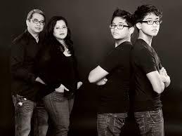 family of four wearing black dark background