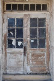 old and vintage exterior double wood doors with glass panels for rustic house design ideas