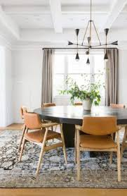 dining room with tan leather chairs and black dining table design via amber interiors