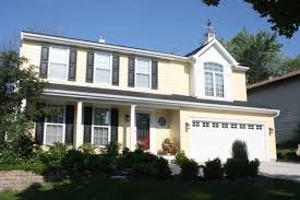 cape cod style yellow siding white trim black shutters red door