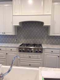 white cabinets and beautiful stone counters in this kitchen are the perfect companions for this backsplash featuring our damask pattern in slate gray