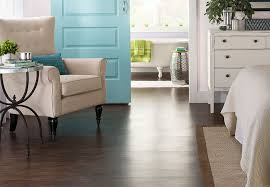 deep tone planks of wood look vinyl flooring in a master bedroom and bathroom