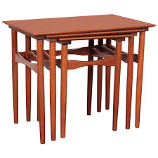 mid century modern comprising three tables of graduated size each table with rectangular top raised on turned tapering